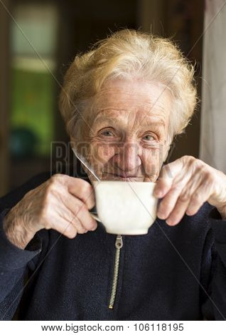 Old woman sits drinking tea, a portrait of an old woman, grandmother.
