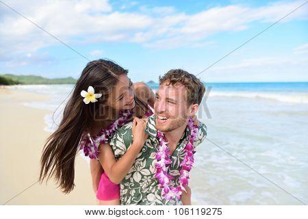 Beach couple having fun laughing on Hawaii holiday. Beautiful Asian mixed race woman piggybacking on Caucasian boyfriend wearing traditional Hawaiian lei on Oahu, Hawaii, USA.
