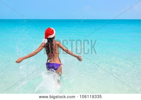 Christmas beach bikini woman swimming in ocean. Beautiful adult entering perfect turquoise water with arms back in freedom feeling free enjoying winter vacations wearing a santa hat for the holidays.