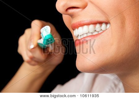 Woman healthy teeth closeup with toothbrush on black background