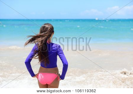 Beach girl going swimming in rashguard swimwear protective clothing. Woman standing in bikini and uv sun protection surf shirt looking at ocean waves. Healthy active lifestyle.