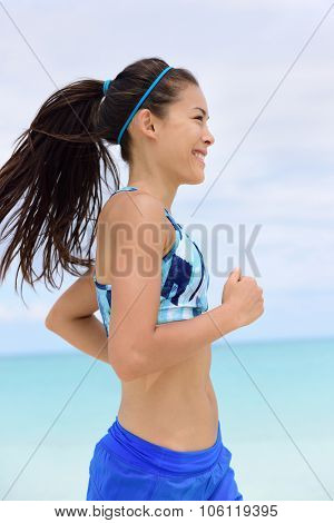 Running woman training her cardio workout in sports bra and hairband doing exercise. Portrait of mixed race Asian Chinese Caucasian young female athlete adult in her 20s happy living a healthy life.