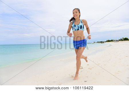 Asian runner woman running on beach living healthy lifestyle. Young adult female athlete training her cardio doing morning jogging barefoot in Caribbean summer destination.