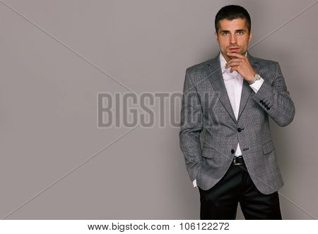Elegant handsome young man in a gray jacket