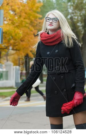Young Woman Hailing Taxi Cab With Holding Out Her One Hand With City Street At Background