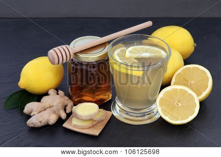 Cold and flu remedy relief drink with ginger, lemon and honey over slate background.