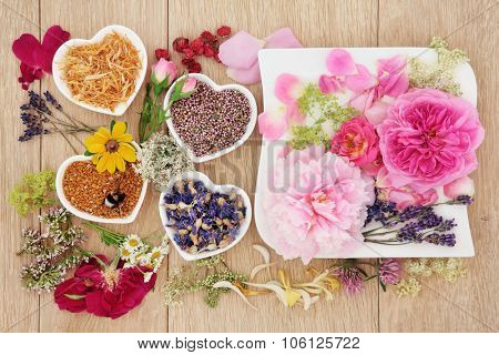 Herb and flower selection used in natural herbal medicine in heart and square shaped dishes with pollen and bee over oak background.