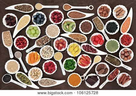 Large health and superfood collection in porcelain dishes over lokta paper background. High in minerals, vitamins and antioxidants.