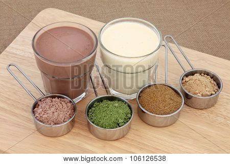 Health and body building food powder supplements and drinks with chocolate whey, wheat grass, pomegranate and maca root, left to right, with protein shakes.