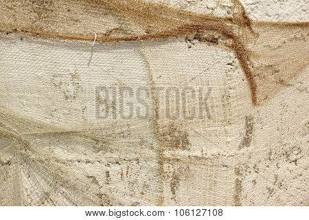 Old Fish Net Hanging And Covered Whitewashed Rustic Concrete Wall