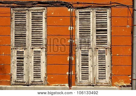 Two Dirty Wooden Closed Shutters In The Old Building Facade