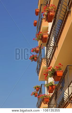 Modern Building With Floral Hanging Baskets On The Balconies Railing