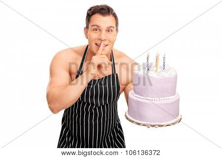 Naked chef with a black apron holding a birthday cake and gesturing silence with finger on his lips isolated on white background