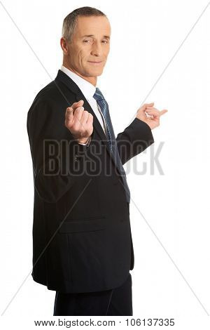 Mature businessman pointing with hands on both sides.