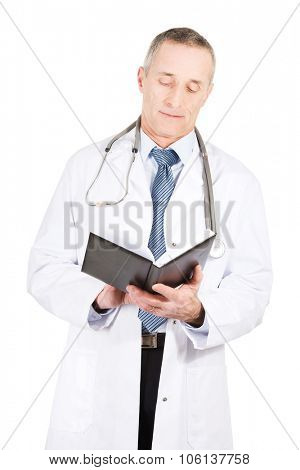 Experienced mature male doctor reading his notes.