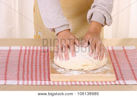 woman hands knead dough on table in home kitchen