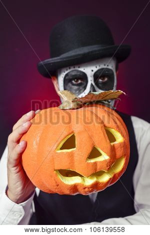 a man with mexican calaveras makeup, wearing bow tie and bowler hat, holds a carved pumpkin in his hand