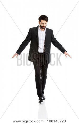 Businessman walking carefully, try to balance himself.