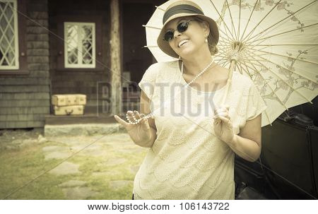 Beautiful 1920s Dressed Girl with Parasol Near Vintage Car, Suitcases and Cabin Portrait.