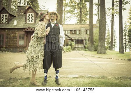 Attractive 1920s Dressed Romantic Couple in Front of Old Cabin Portrait.