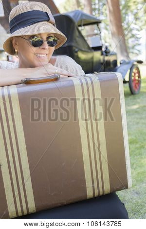 Pretty 1920s Dressed Girl With Suitcase With Room For Text Near Vintage Car and Cabin.