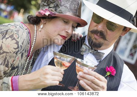 Attractive Mixed-Race Couple Dressed in 1920s Era Fashion Sipping Champagne.