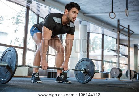 Athlete wearing blue shorts and black t-shirt lifting big barbell