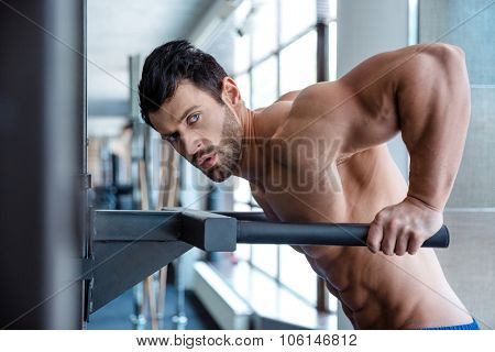 Portrait of a muscular man workout on parallel bars in fitness gym and looking at camera