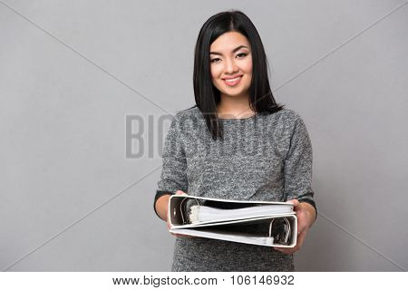 Beautiful happy smiling asian girl in gray jumper looking at camera holding documents in two folders