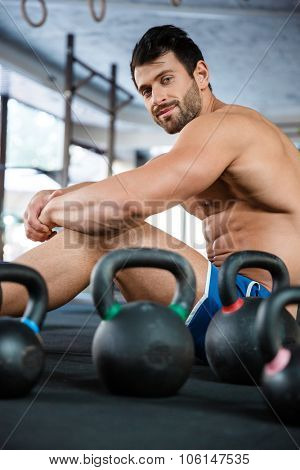 Portrait of a happy muscular man sitting in fitness gym with kettle balls and looking at camera