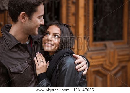 Portrait of a happy couple hugging outdoors with old wooden door on background