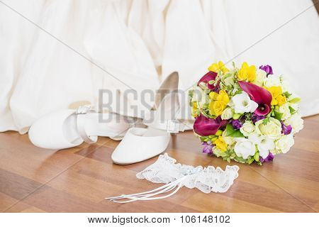 Brides wedding shoes, garter, and flowers sitting on the floor