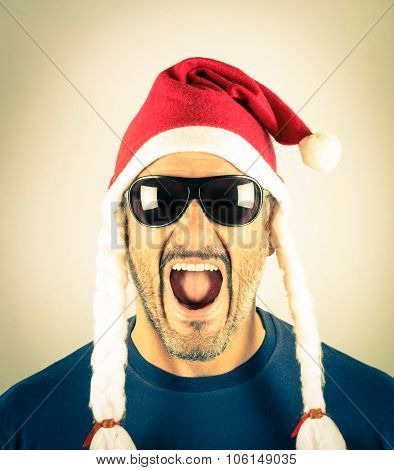 Portrait Of A Desperate Young Man With Santa Claus Red And Sunglasses - Concept Of Crazy Christmas