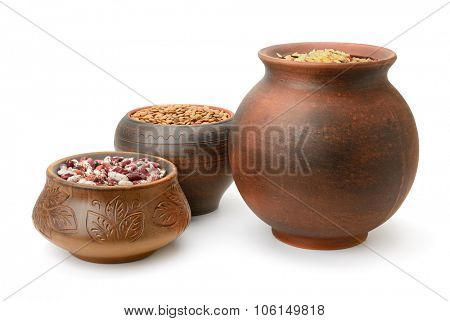 Beans, rice and lentils in pots isolated on white