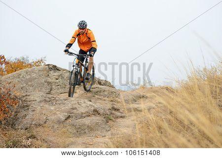 Cyclist in Orange Wear Riding Bike on the Beautiful Autumn Mountain Trail