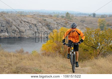 Cyclist in Orange Wear Riding Bike on the Beautiful Autumn Mountain Trail under River