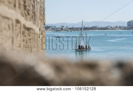 Acre, Israel- Sptembet 9, 2015: sailing boat in the sea through the Acre wall