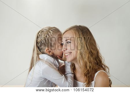 Mother and daughter sharing a secret indoors