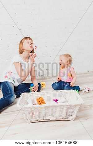 Nice girl blowing bubbles to her little sister