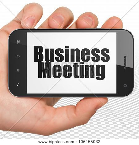 Business concept: Hand Holding Smartphone with Business Meeting on display