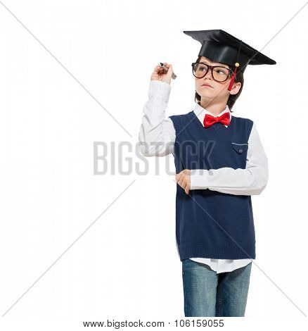 Graduated little boy wearing mortarboard and holding pen isolated on white background. Serious scholar boy writing with pen message over white background. Concentrated schoolboy with graduation hat.