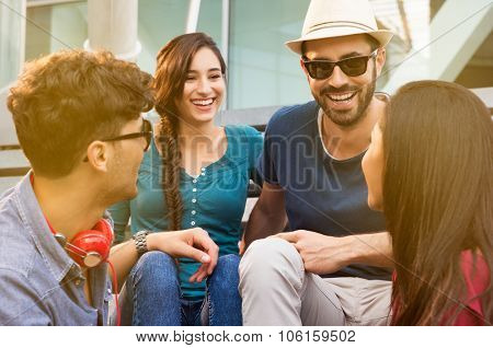 Portraits of young happy friends smiling and sitting on staircase having fun. Women and men laughing together outdoor in a summer day. Smiling girls and guys having fun sitting on staircase.