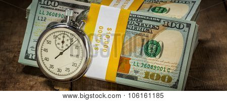 Time is money loan concept background -  letterbox panorama of stopwatch and stack of new 100 US dollars 2013 edition banknotes (bills) bundles on wooden background