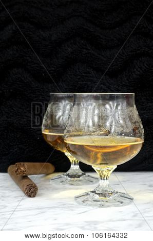 Two Glasses Of Cognac With A Cigar On A Marble Table
