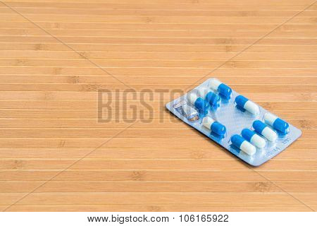 Blue And White Pills In Blister On A Wooden Table
