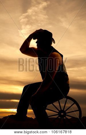 Silhouette Cowboy Sitting On Wagon Wheel Touch Hat