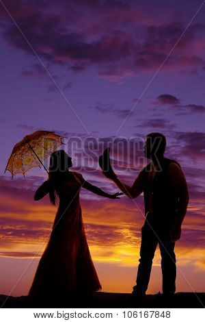 Silhouette Of Cowboy And Woman With Umbrella Looking At Eachother Sunset