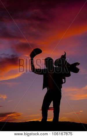 Silhouette Of A Cowboy Holding His Hat Up And A Saddle On Shoulder