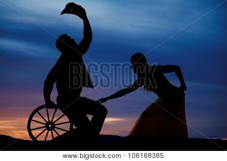 Silhouette Of Cowboy On Wagon Wheel And Woman In Sunset