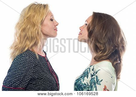 Two blond women looking at each other